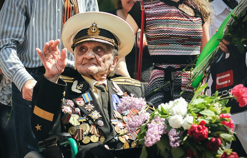 Sevastopol, Ukraine - May 9, 2012: an old World War II veteran in a wheelchair with flowers at the parade during the celebration o. F `Victory Day` over Nazi stock images