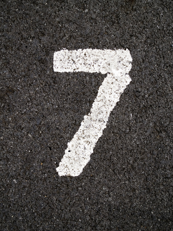 Seven. A close up on white stenciled number seven on black pavement royalty free stock photography