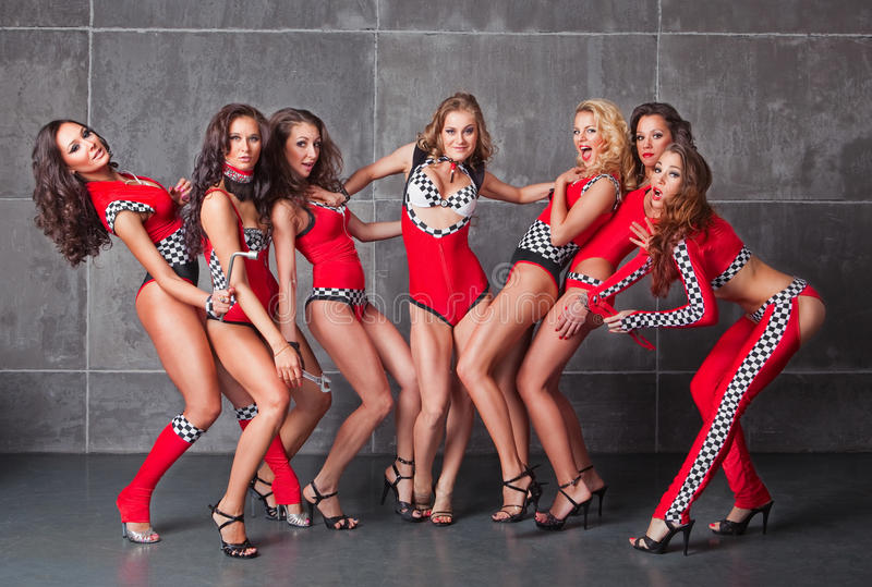 Seven Cute go-go girls in red racing costume. Ready to go party stock photography