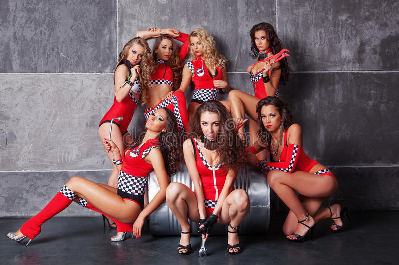 Seven Cute go-go girls in red racing costume royalty free stock image