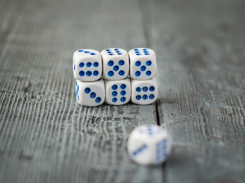 Seven dice are stacked in a pile on a wooden dark table. stock photography