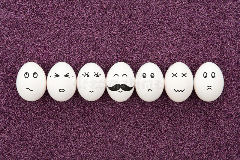Seven eggs on purple sand. Seven eggs with different facial expressions are lying on the decorative purple sand royalty free stock images