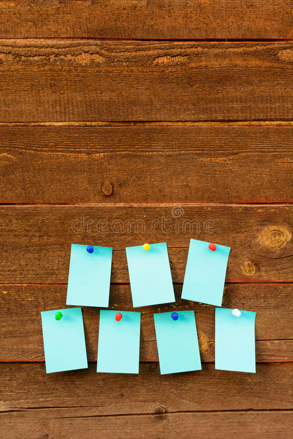 Seven empty blue paper with colorful pins over wooden background stock images