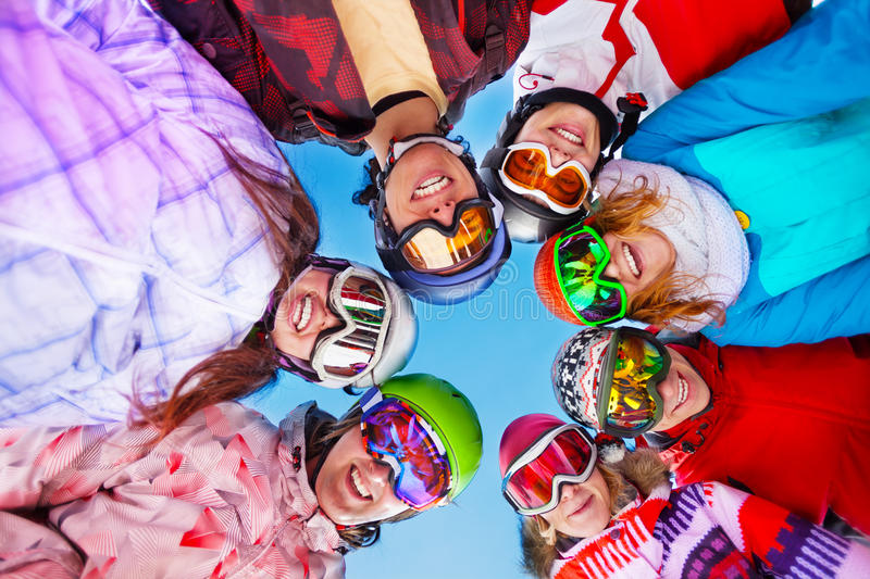 Seven happy friends in circle wearing goggles royalty free stock photo