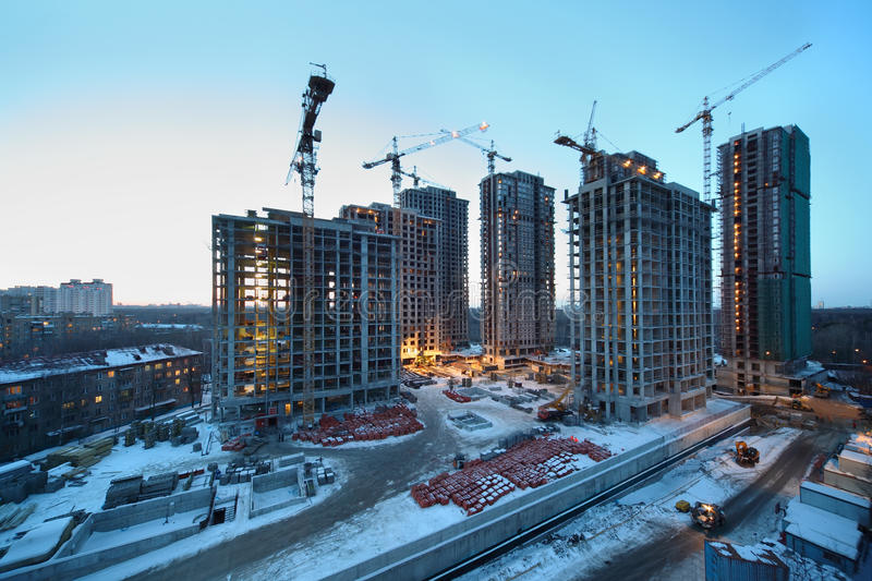 Seven high buildings under construction. With cranes at day, red bricks and other building materials royalty free stock images