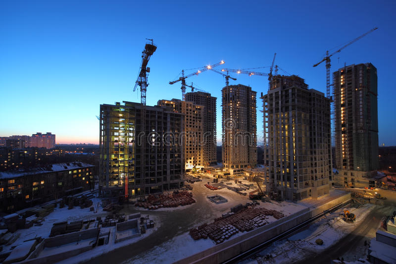 Seven high buildings under construction. With cranes at evening royalty free stock images