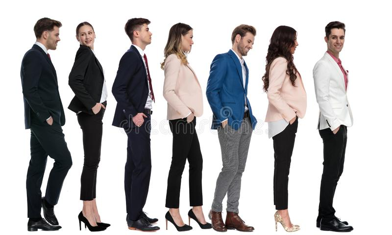 Seven modern young business people waiting in line stock photography