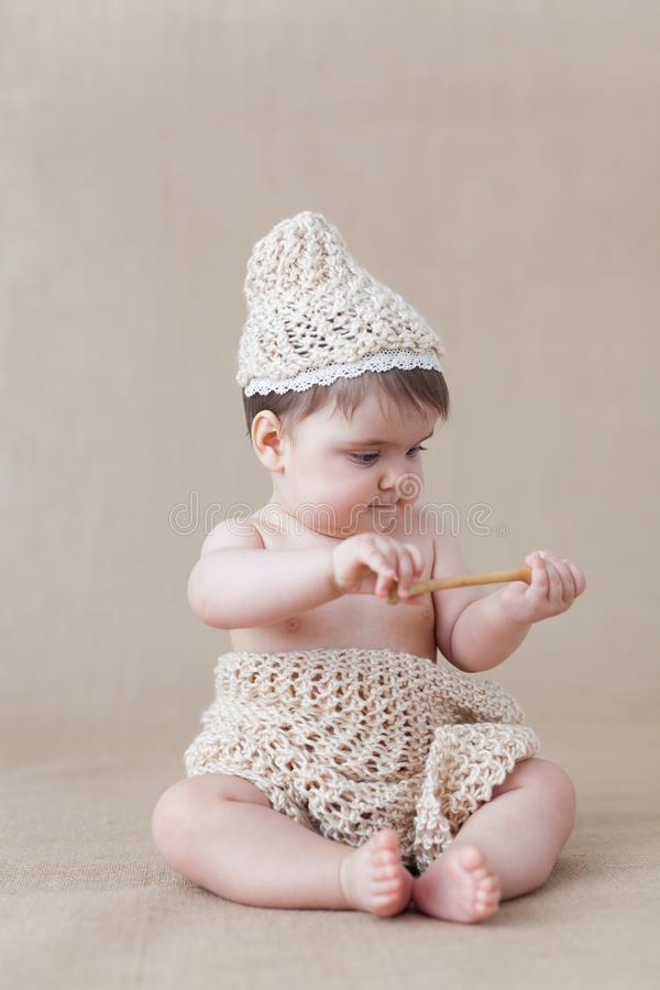 Baby girl playing with a wooden honey spoon royalty free stock photos