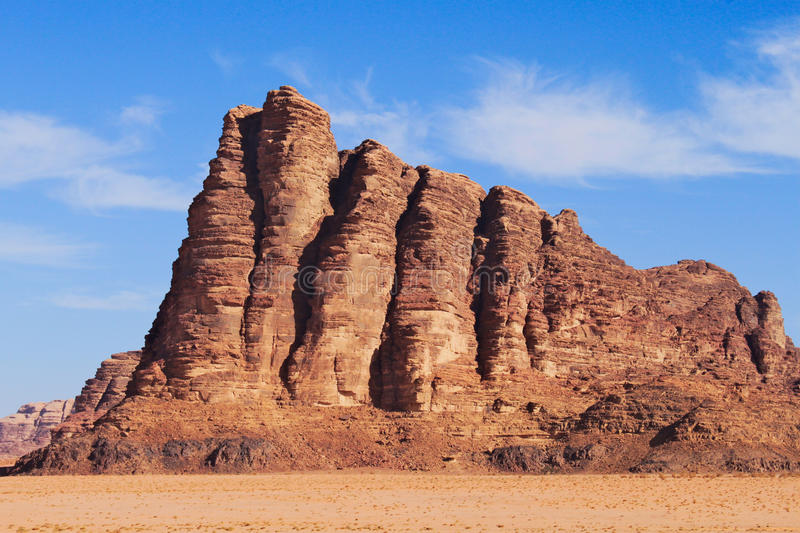 Seven pillars of wisdom on Wadi Rum desert in Jordan. Around red sand and clear blue sky with few clouds royalty free stock image