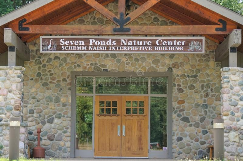 Seven Ponds Nature Center, Metamora, Michigan, August 2019. The Schemm-Nash Interpretive Building front doors, river eroded stone walls and red wood peaked stock images