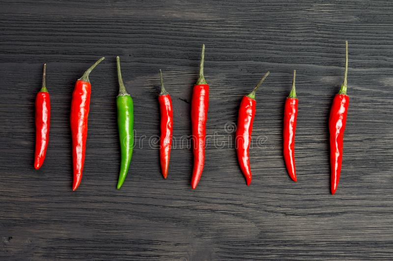 Seven red and one green hot pepper. On a wooden table royalty free stock photos