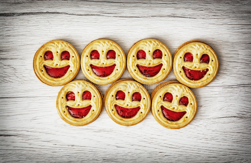 Seven round biscuits smiling faces, humorous food theme royalty free stock image