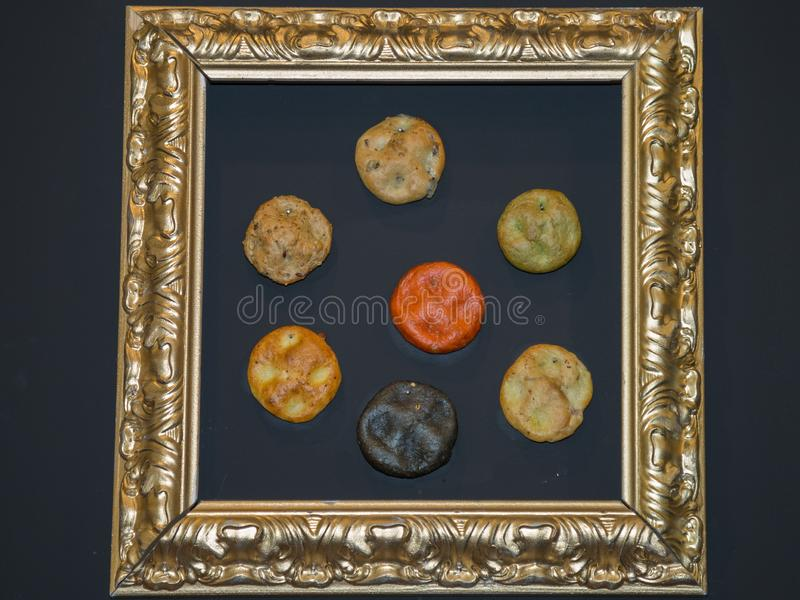 Seven Soft Coloured Flat Cakes in a Frame, Wooden background royalty free stock photography