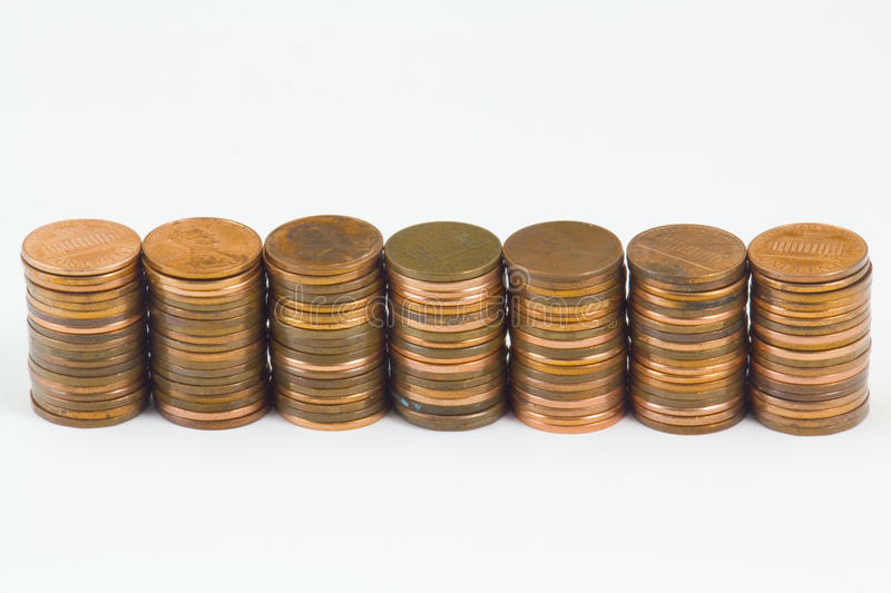 Seven stacks of American cents. Seven stacks of American cent coins in a row isolated on a white background royalty free stock images