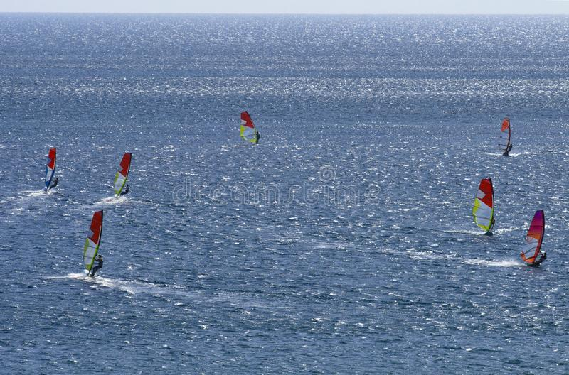 Seven windsurfers are riding on the surface of the dazzling beautiful Mediterranean sea. On Cape Prasonisi Rhodes, Greece stock photography