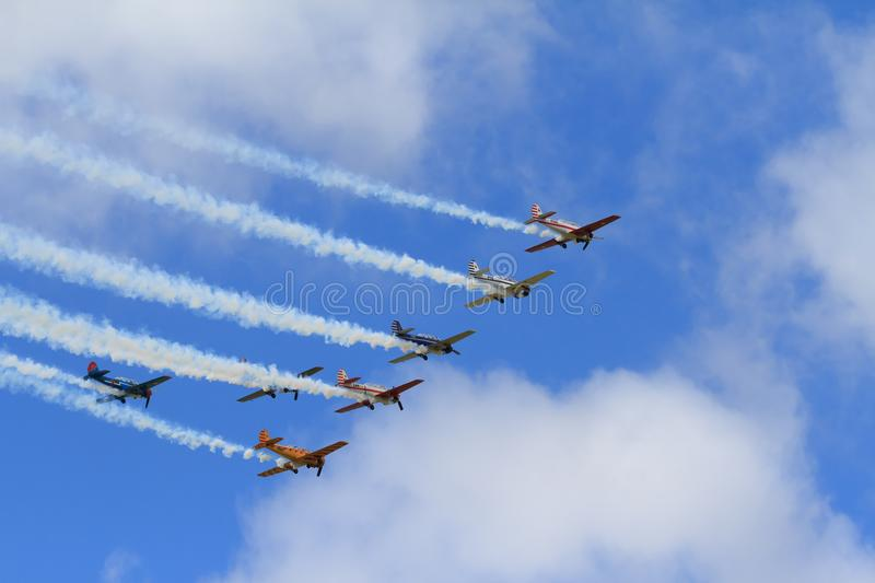 Seven Yak-52 airplanes flying formation, trailing smoke stock photography