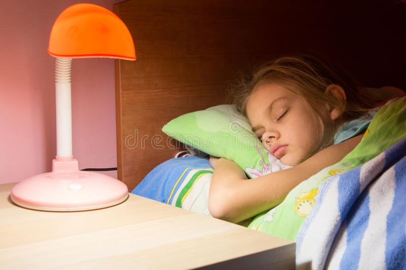 Seven-year girl asleep in bed, reading lamp is included on the next table. Seven-year girl asleep in bed, reading lamp is included on next table stock image