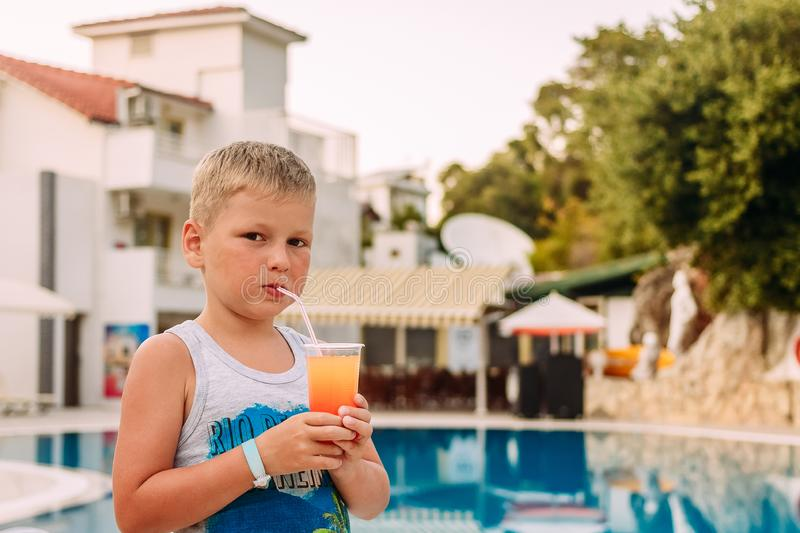 Seven-year-old blonde tanned boy drinking orange non-alcoholic cocktail from a tube outdoors. Seven-year-old blonde tanned boy drinking orange non-alcoholic royalty free stock image