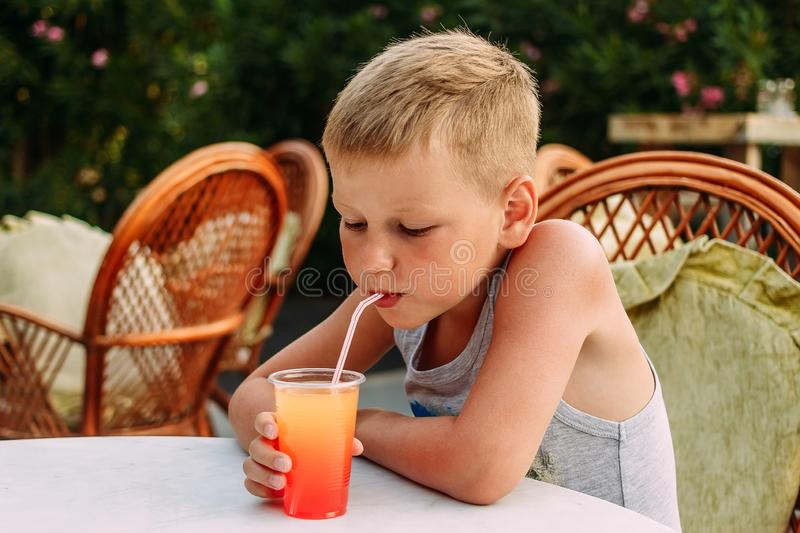 Seven-year-old blonde tanned boy drinking orange non-alcoholic cocktail from a tube in a summer restaurant. Outdoors royalty free stock photo
