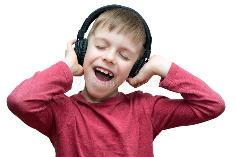 Seven year old boy with headphones singing on white. Background royalty free stock photography