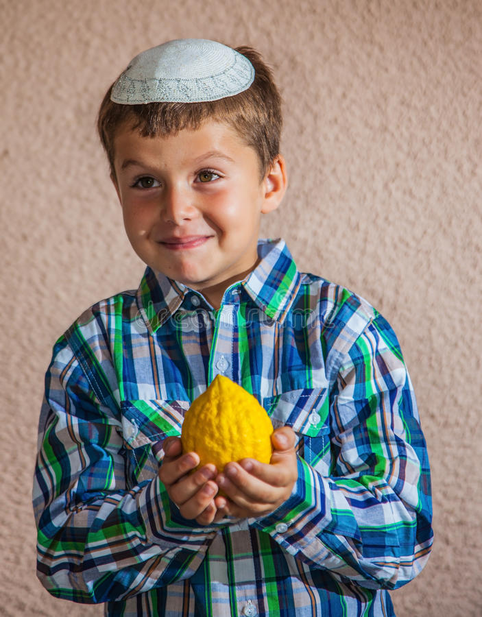 The seven year old boy is holding citron. Citron - ritual fruit for the Jewish holiday of Sukkot. Beautiful seven year old boy in white knitted skullcap is royalty free stock photography
