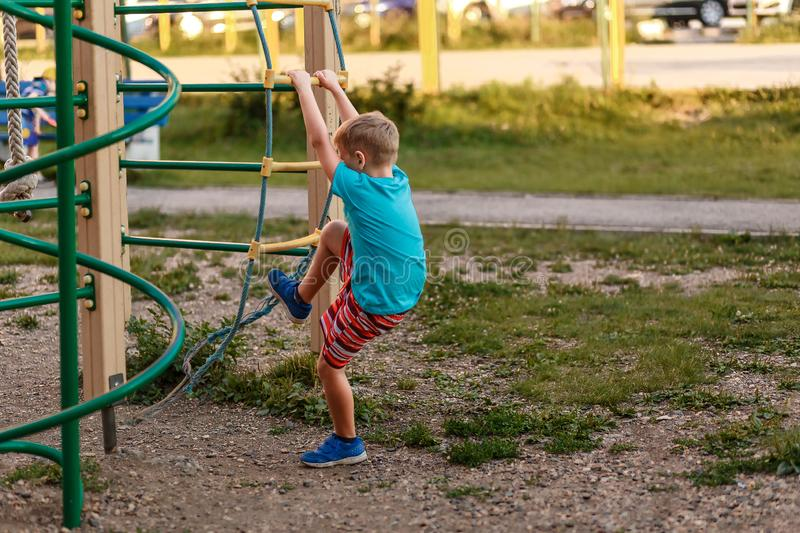 Seven-year-old boy in shorts climbs in the summer on the Playground stock photography
