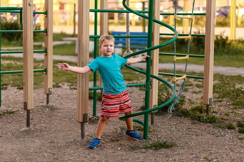 Seven-year-old boy in shorts playing in the summer on the Playground royalty free stock photos
