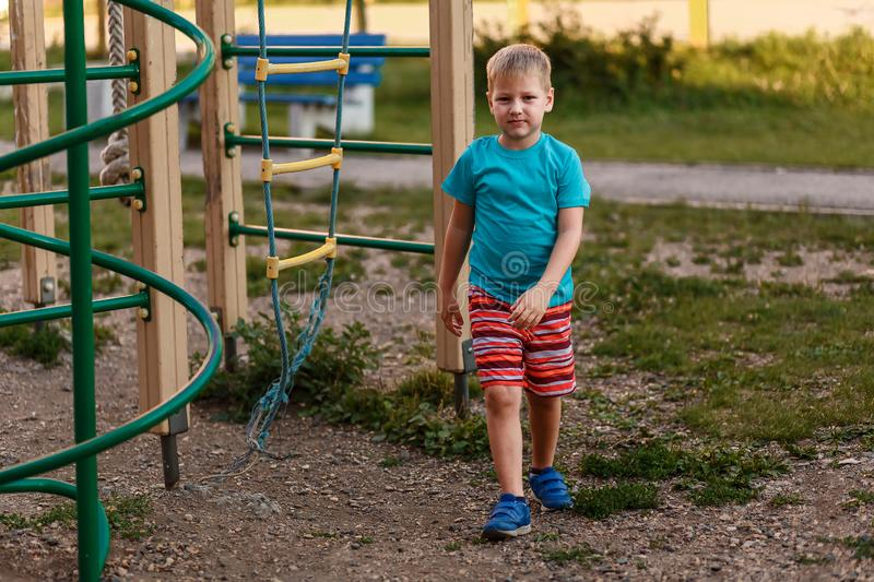 Seven-year-old boy in a turquoise t-shirt and red shorts in the summer on the Playground royalty free stock image