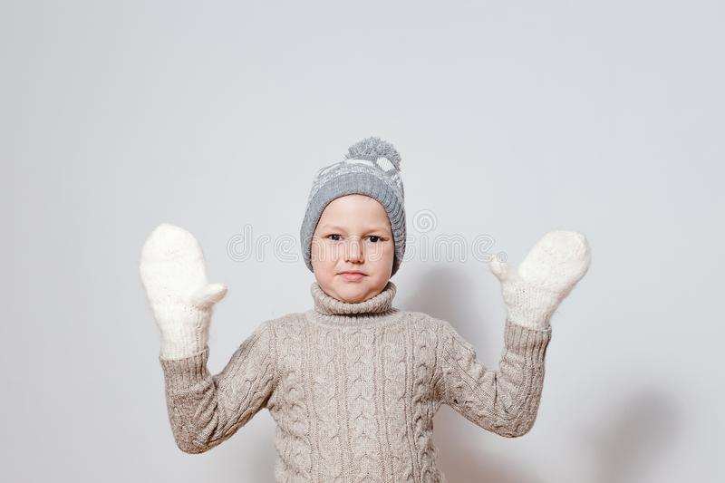 Seven-year-old boy in white knitted mittens and sweater spreads his hands to the sides. On a white background stock photography