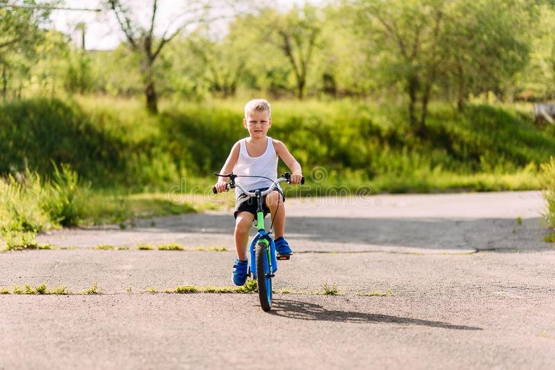 Seven-year-old boy in a white t-shirt rides a children`s blue bike outdoors in the summer. Seven-year-old boy in a white t-shirt rides a children`s blue bike on royalty free stock photo