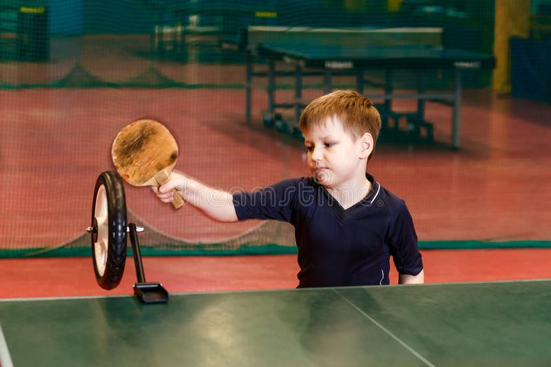 Seven-year-old child in gray form trains strikes in table tennis with the help of a robot on the table royalty free stock image