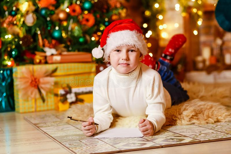 A seven-year-old child lies on a soft fluffy blanket on his stomach and writes a letter to Santa Claus stock image