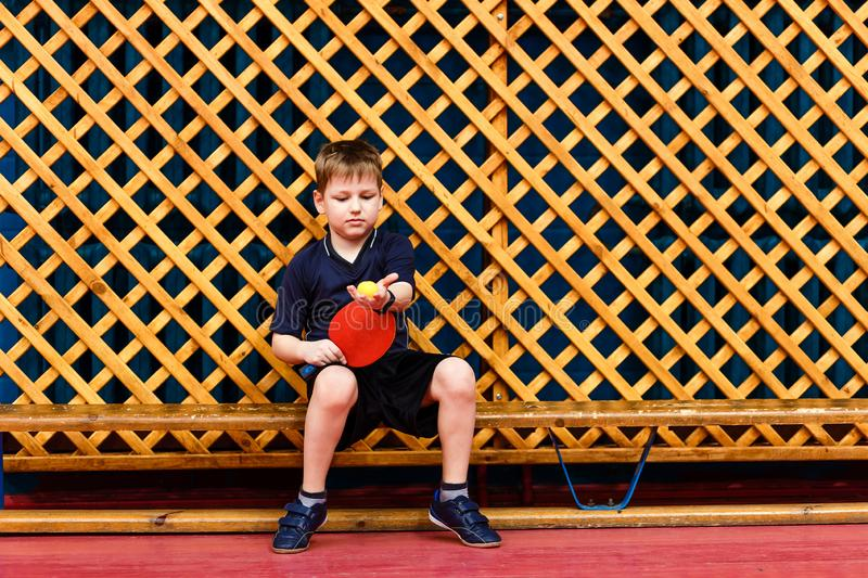 Seven year old child sits on the bench with a tennis racket royalty free stock images
