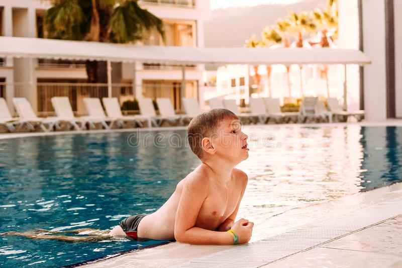 Seven-year-old child in swimming shorts swam to the edge of the pool in the outdoor pool stock photos