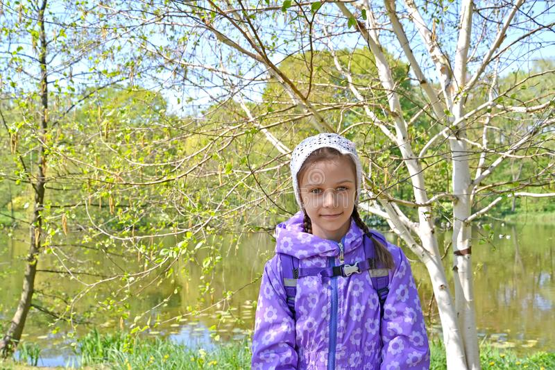 The seven-year-old girl against the background of the blossoming trees in the park. Spring stock image