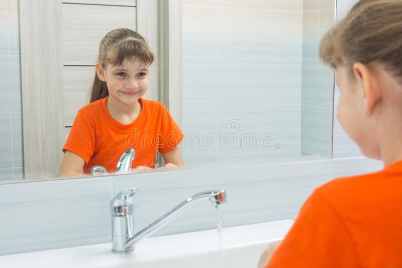 Seven-year-old girl washing her face looks at herself stock photo