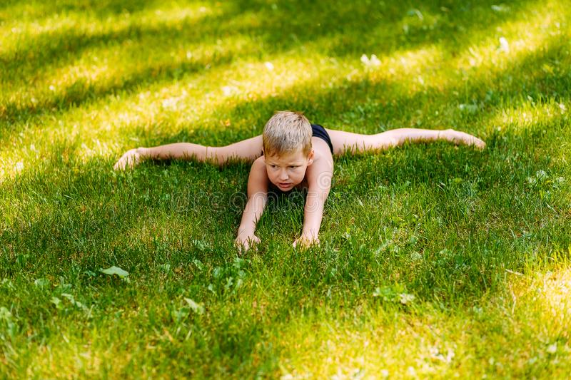 Seven-year-old tanned boy in bathing trunks performs acrobatic exercise. `cross twine` in the summer on the green grass royalty free stock photography
