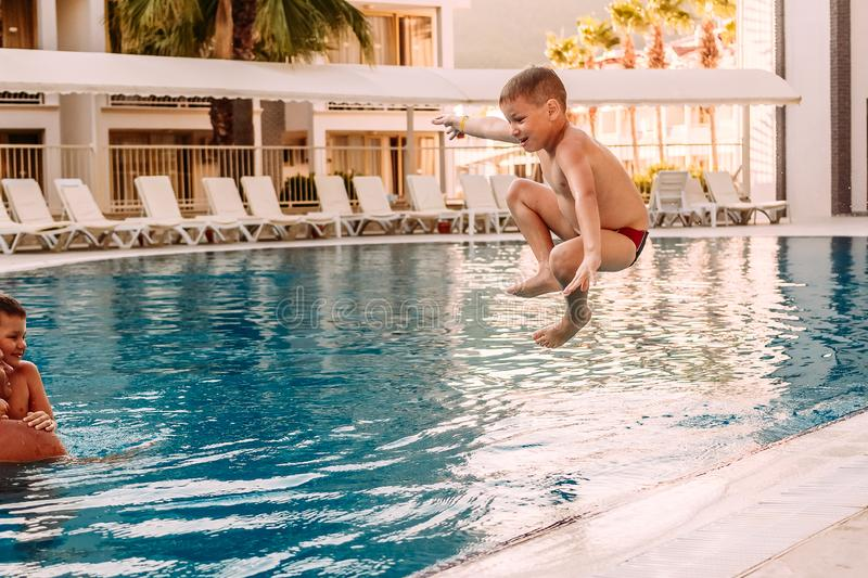 Seven-year-old tanned boy jumping, legs tucked in the outdoor pool at the resort royalty free stock photos