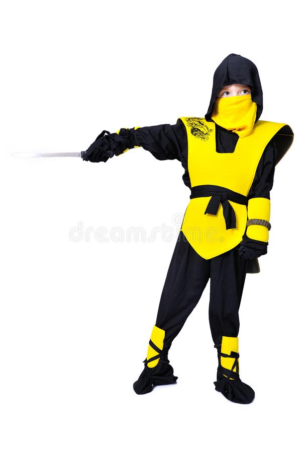 The seven-years old boy in black and yellow ninja suit with a ho. A boy in black and yellow ninja suit with a hood and mask on his face bowed his head. With a stock photography