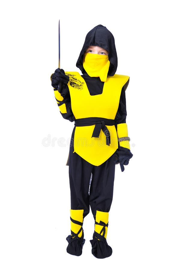 The seven-years old boy in black and yellow ninja suit with a ho. A boy in black and yellow ninja suit with a hood and mask on his face bowed his head. With a royalty free stock images