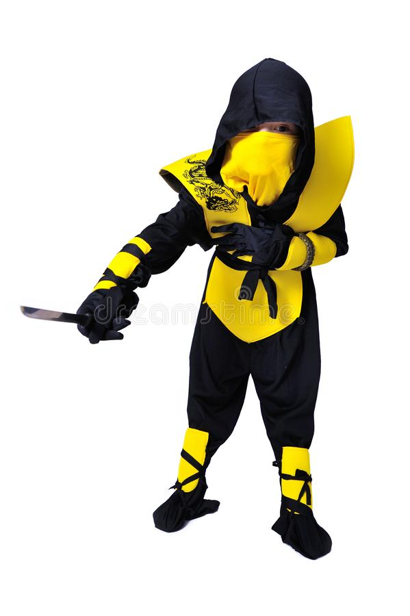 The seven-years old boy in black and yellow ninja suit with a ho. A boy in black and yellow ninja suit with a hood and mask on his face bowed his head. With a stock images