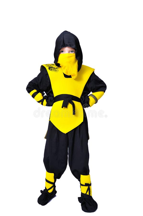 The seven-years old boy in black and yellow ninja suit with a ho. A boy in black and yellow ninja suit with a hood and mask on his face bowed his head. With a stock image