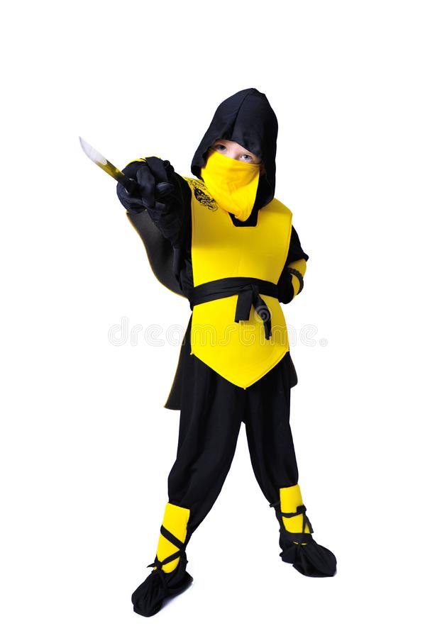 The seven-years old boy in black and yellow ninja suit with a ho. A boy in black and yellow ninja suit with a hood and mask on his face bowed his head. With a stock photo