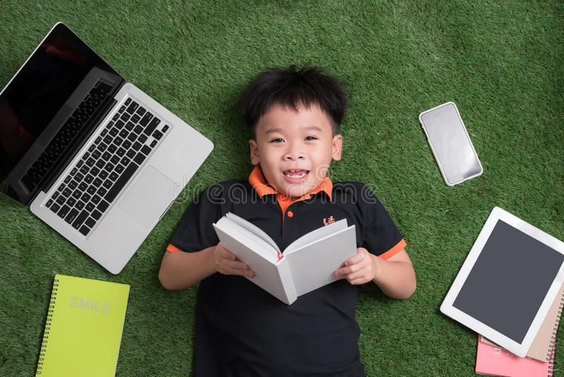Seven years old child reading a book lying on the grass.  stock photos