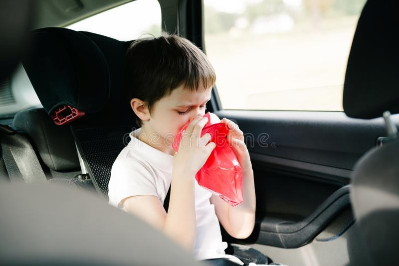 Seven years old child vomiting in car. Suffers from motion sickness stock photography