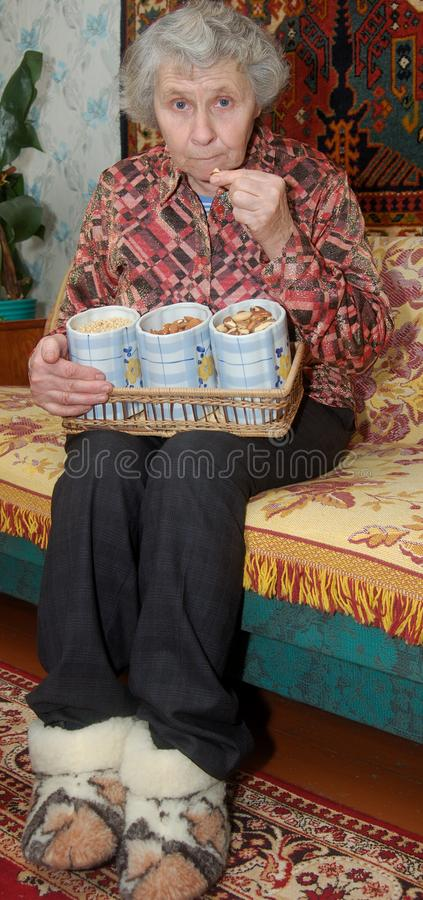 Seventy year old woman cracks nuts royalty free stock image