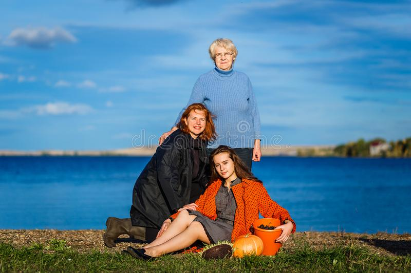 A seventy-year-old woman, a forty-year-old woman, and a twenty-year-old woman. Three generations of women in the family outdoors. royalty free stock image