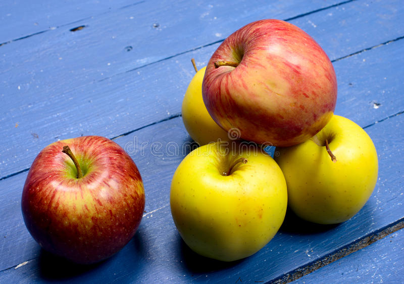 Several apples placed on a table painted blue stock photography