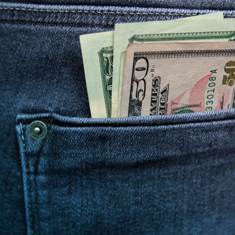 Several banknotes of 20 and 50 American dollars are in the back pocket of men`s blue jeans, square, close-up stock image