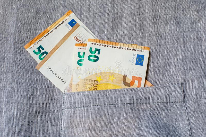 Several banknotes of 50 euros are in a canvas pocket. The concept of earning, saving or spending money royalty free stock images